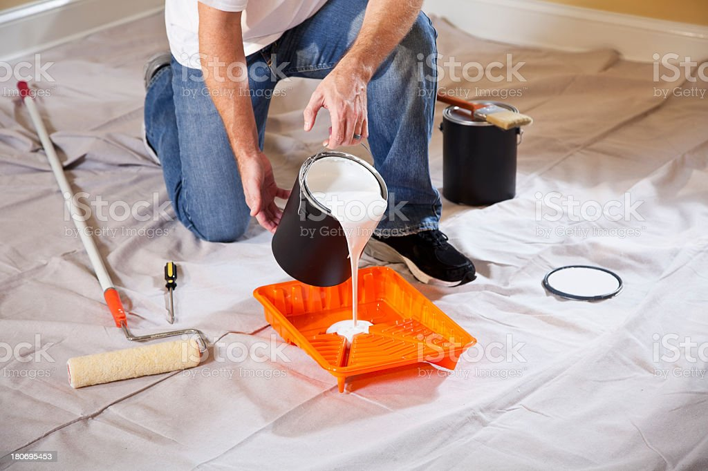 Man pouring paint into tray stock photo