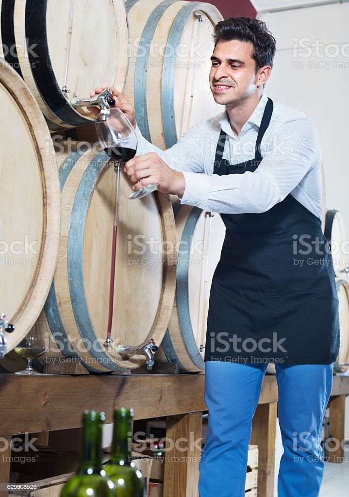 Man pouring red wine into glass in alcohol section stock photo
