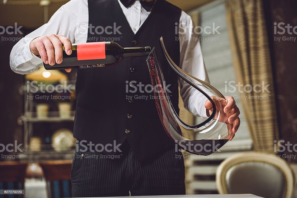 Man pouring red wine into graceful decanter stock photo