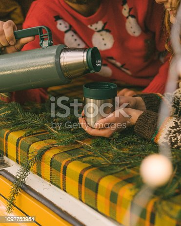 Young Caucasian man pouring tea from thermos into cup in camper van