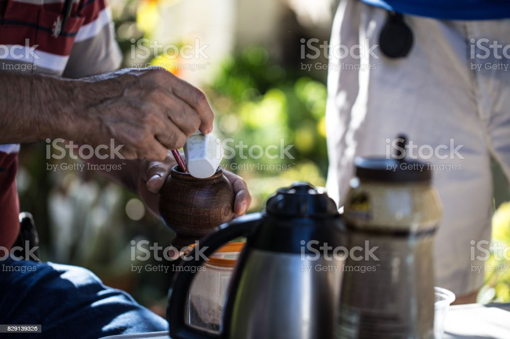 Man pouring water into yerba mate cup stock photo