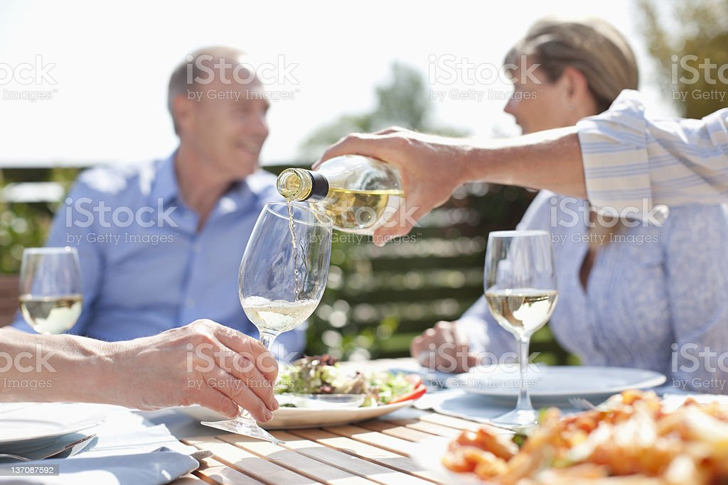 Homem servindo vinho em uma mesa de sol - foto de acervo