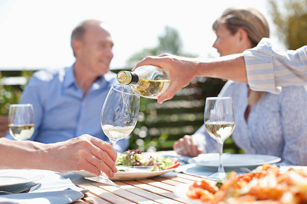 Man pouring wine at sunny table  white wine stock pictures, royalty-free photos & images