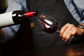 Man pouring wine into wineglass, male hand holding bottle of red expensive alchoholic beverage, closeup photo