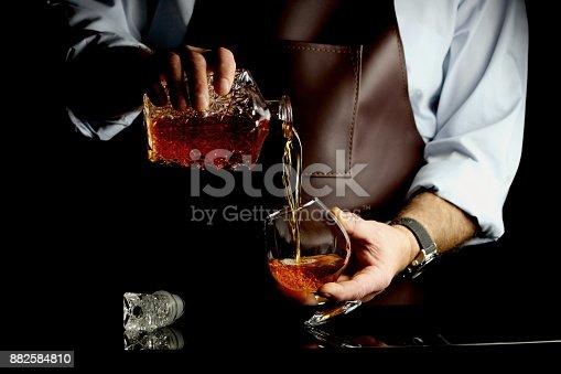 istock man pours cognac 882584810