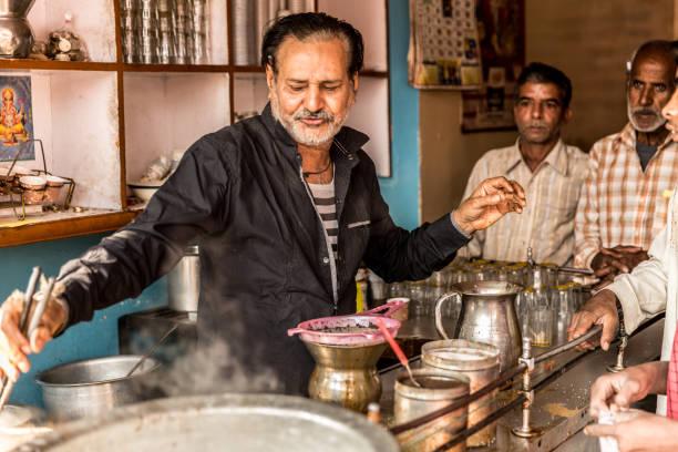 man gießt tasse heiße milch tee (masala chai) indischen stil - teeladen stock-fotos und bilder