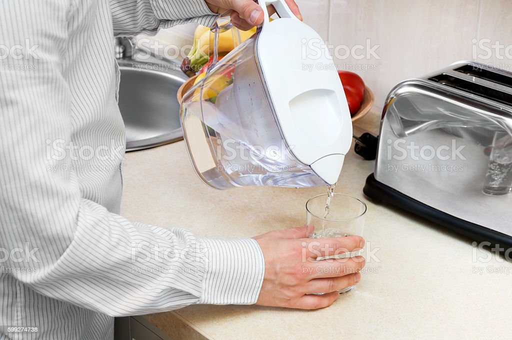 Man pours filtered water into the glass stock photo