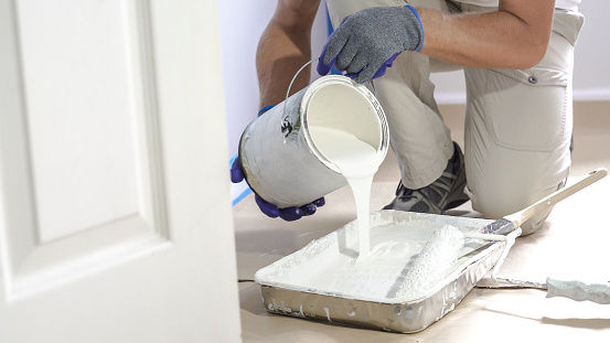 Man pours paint into the tray and dips roller. Professional interior construction worker pouring white color paint to tray.