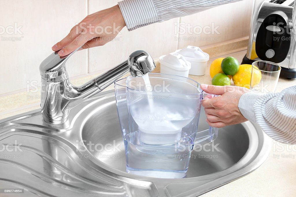 Man pours water into water filter jug stock photo