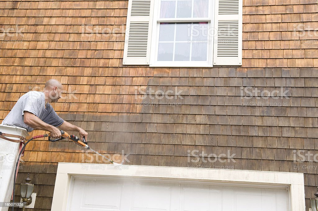 Man Power Washing exterior shingles royalty-free stock photo
