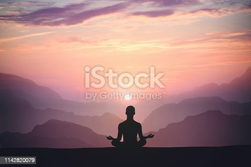 Man practices yoga and meditates on the mountain and sunset