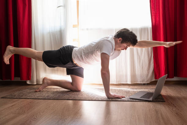 Man practices yoga asana chakravakasana or bird pose at the living room stock photo