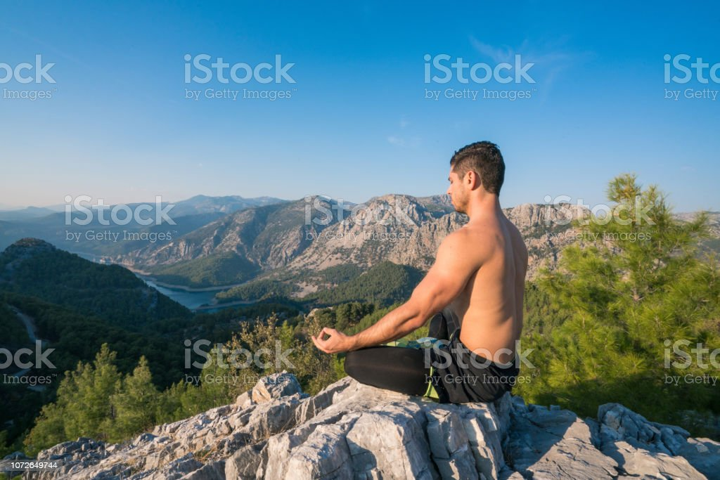 A man practices yoga at the top of the mountain A man practices yoga at the top of the mountain  Practices of relaxation Achievement Stock Photo