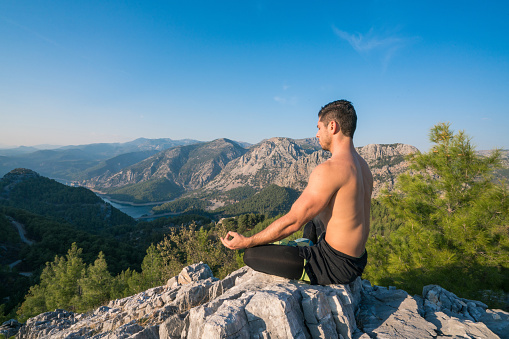 A Man Practices Yoga At The Top Of The Mountain Stock Photo - Download Image Now