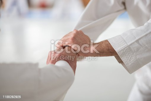 Shaking hands. Man practicing aikido shaking hands of his rival before starting fight