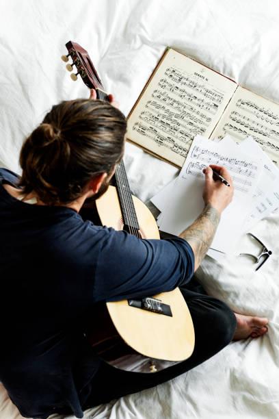 menschen üben notizen mit gitarre - musiknoten tattoos stock-fotos und bilder