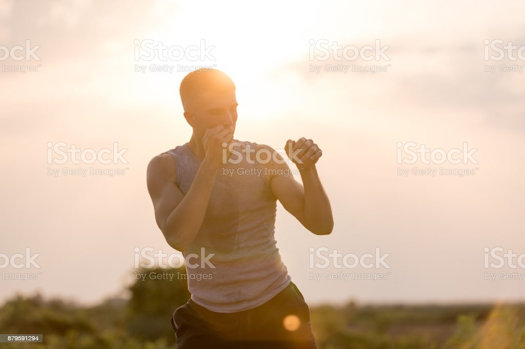 Man practicing shadow boxing outdoors stock photo