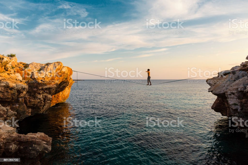 Man practicing slackline over the sea stock photo
