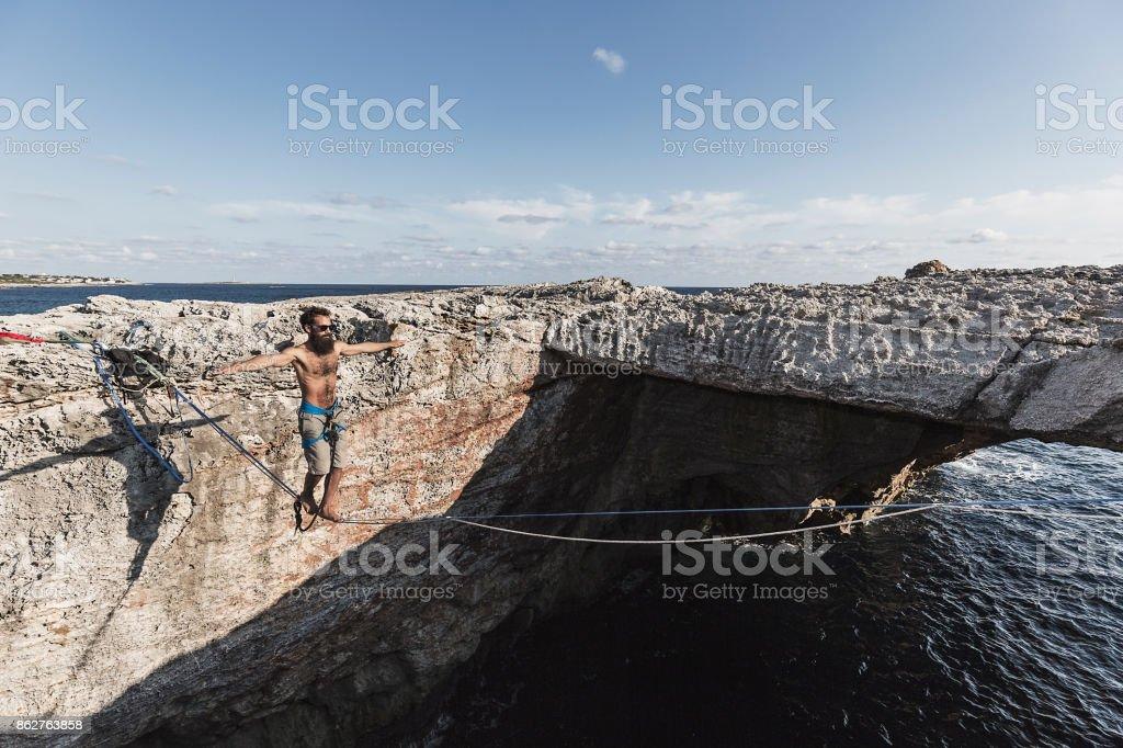 Man practicing slacklining at the sea stock photo