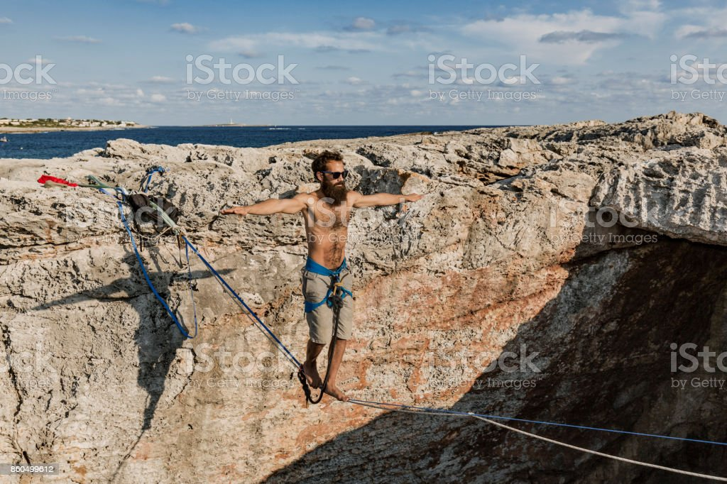 Man practicing slacklining over the sea stock photo