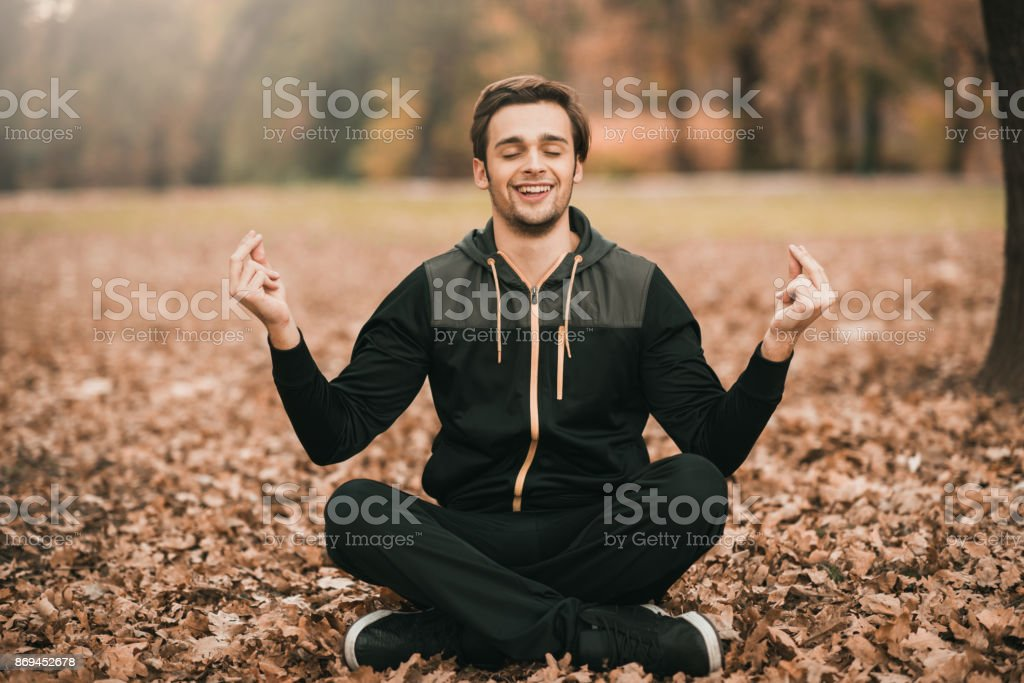 Man practicing yoga and meditating in the woods stock photo