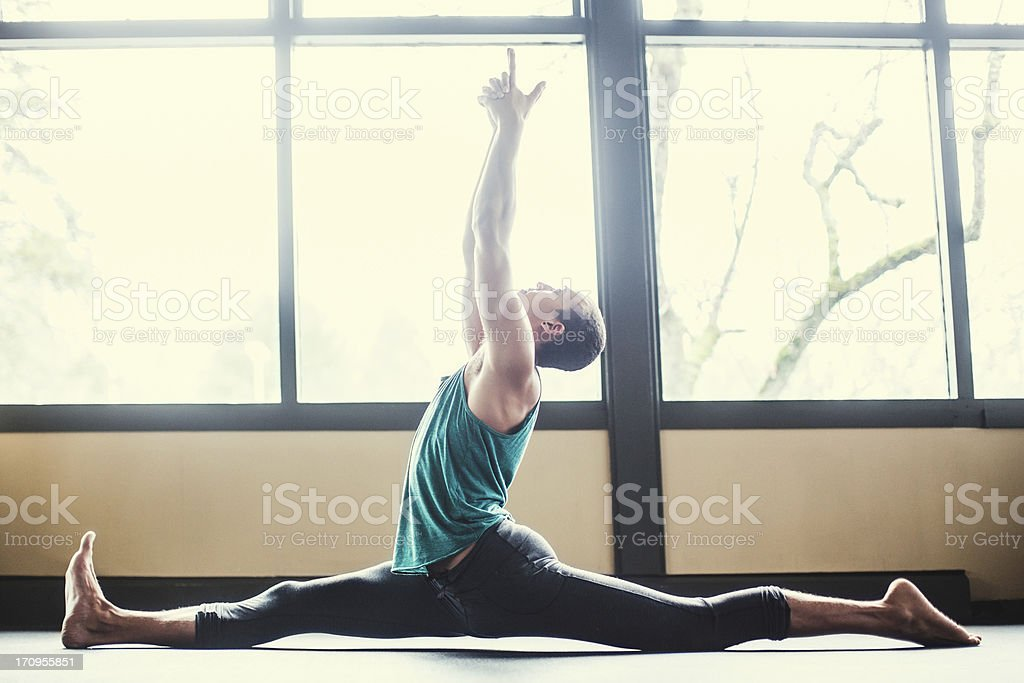 Man Practicing Yoga in Bright Studio stock photo