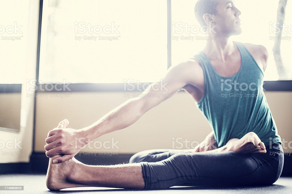 Man Practicing Yoga in Bright Studio stock photo