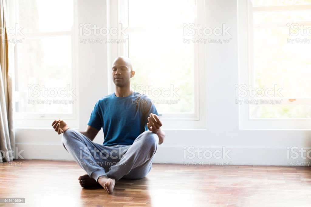 Man practicing yoga in lotus position at home stock photo