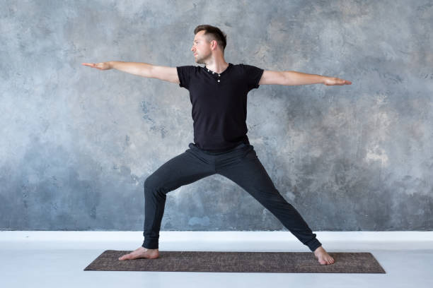 Man practicing yoga in studio doing Warrior 2 pose stock photo