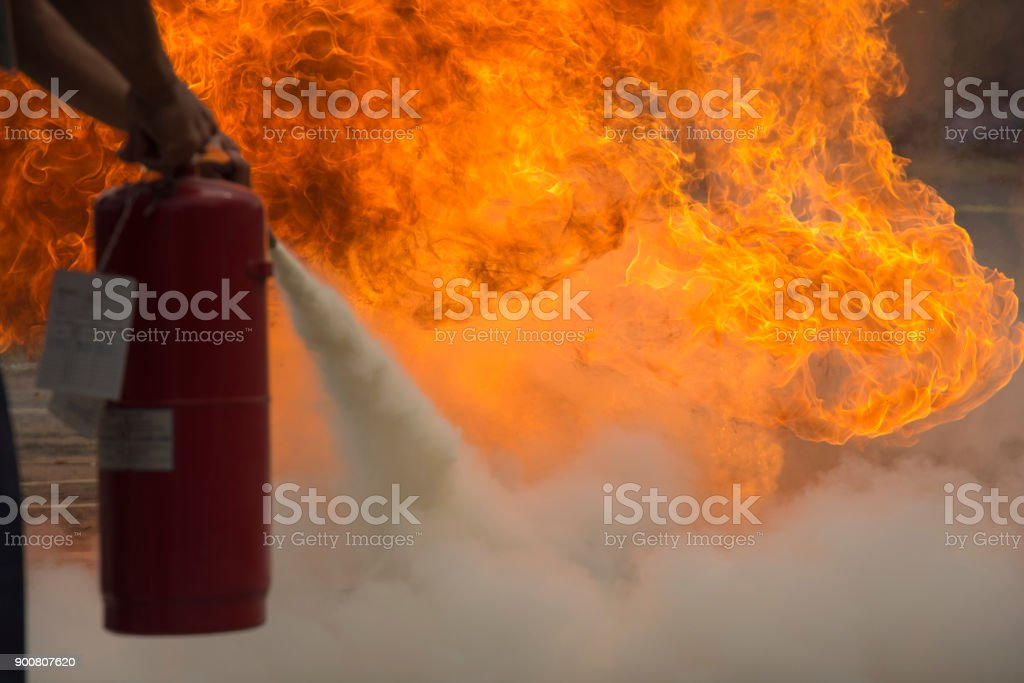 A man practises how to use a fire-extinguisher stock photo