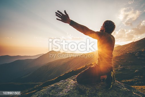 Man praying at sunset mountains raised hands Travel Lifestyle spiritual relaxation emotional concept vacations outdoor harmony with nature landscape