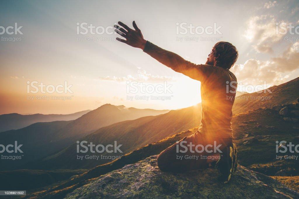 Mann, der betet bei Sonnenuntergang Bergen die erhobenen Hände Reisen Lifestyle geistige Entspannung emotionales Konzept Urlaub im freien Harmonie mit der Naturlandschaft – Foto
