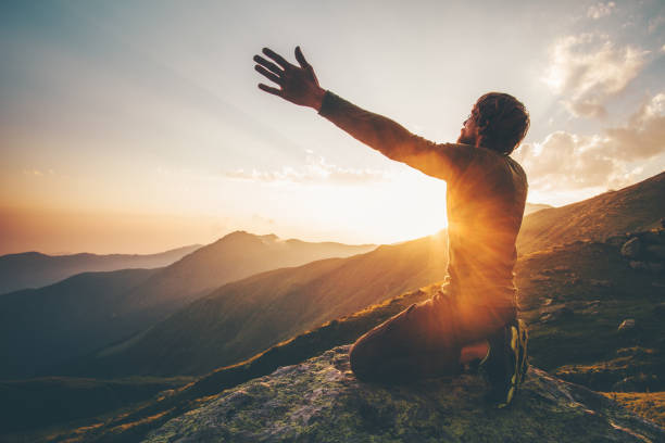 man praying at sunset mountains raised hands travel lifestyle spiritual relaxation emotional concept vacations outdoor harmony with nature landscape - religion stock pictures, royalty-free photos & images