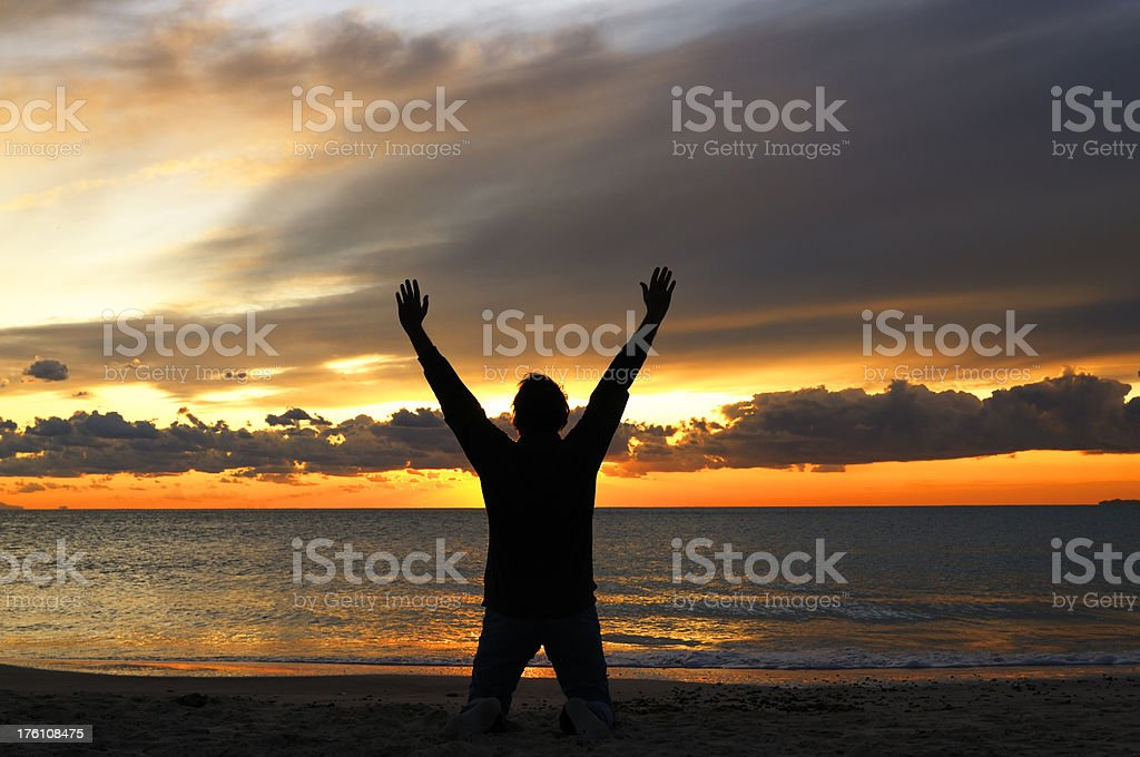 Man Praying by the Sea at Sunset royalty-free stock photo