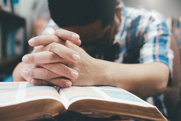 Man praying, hands clasped together on her Bible. stock photo