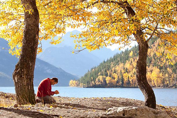 mann beten im herbst an einem wunderschönen mountain lake - gott sei dank stock-fotos und bilder