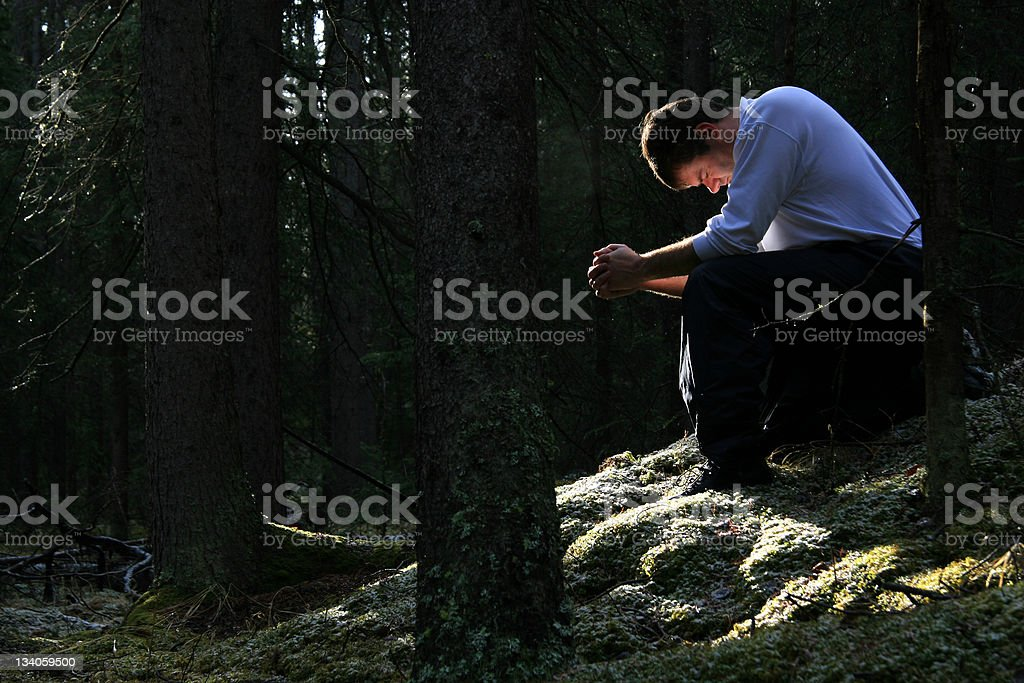 Man Praying in the Forest stock photo