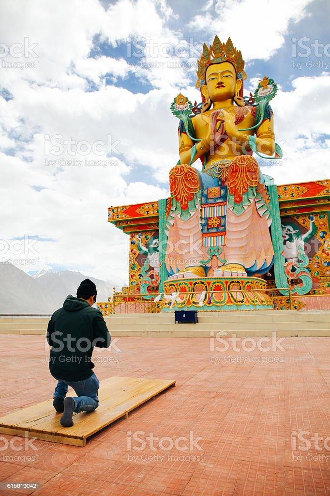 Man praying in Tibetan Buddhist temple of Maitreya in Ladakh stock photo