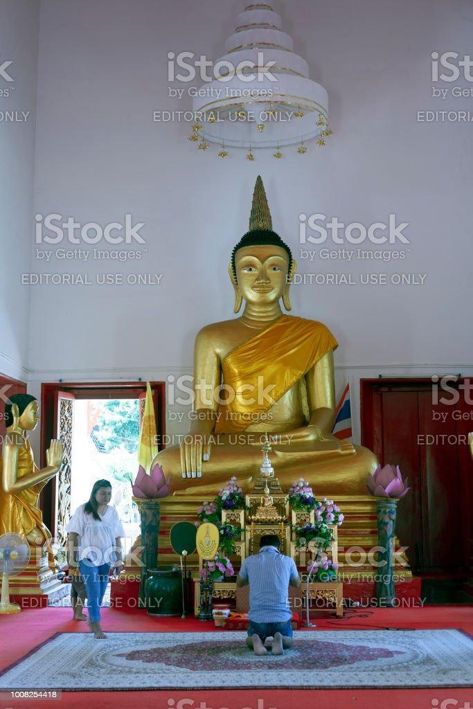 Man praying in Wat Mongkol Nimit temple stock photo