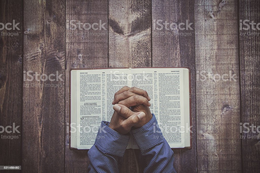 Man praying on a wooded table stock photo