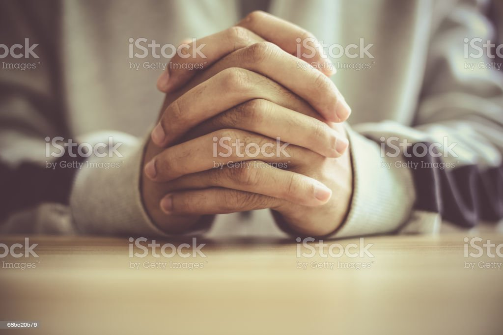 Hombre orando en una mesa de madera - foto de stock