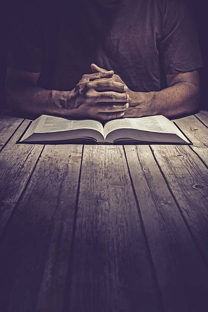 Man praying on a wooden table with an open Bible stock photo
