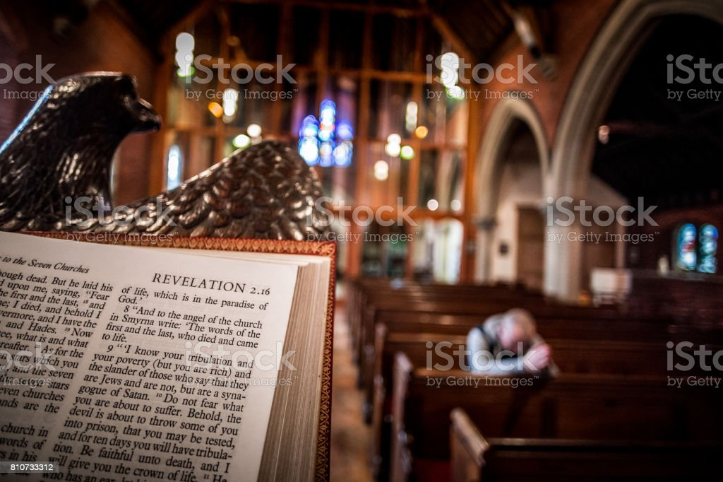 Man praying on pew inside English Anglican church with focus on bible in foreground stock photo