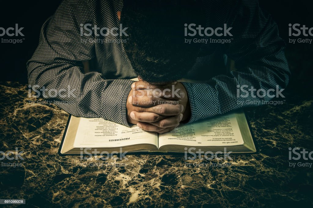 Man praying to God on an open Bible stock photo