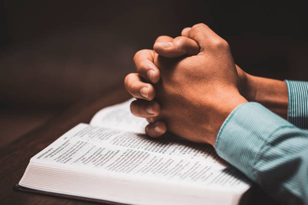 Man praying with his hands on a bible stock photo