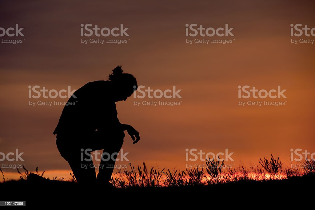 Man prays at sunset stock photo