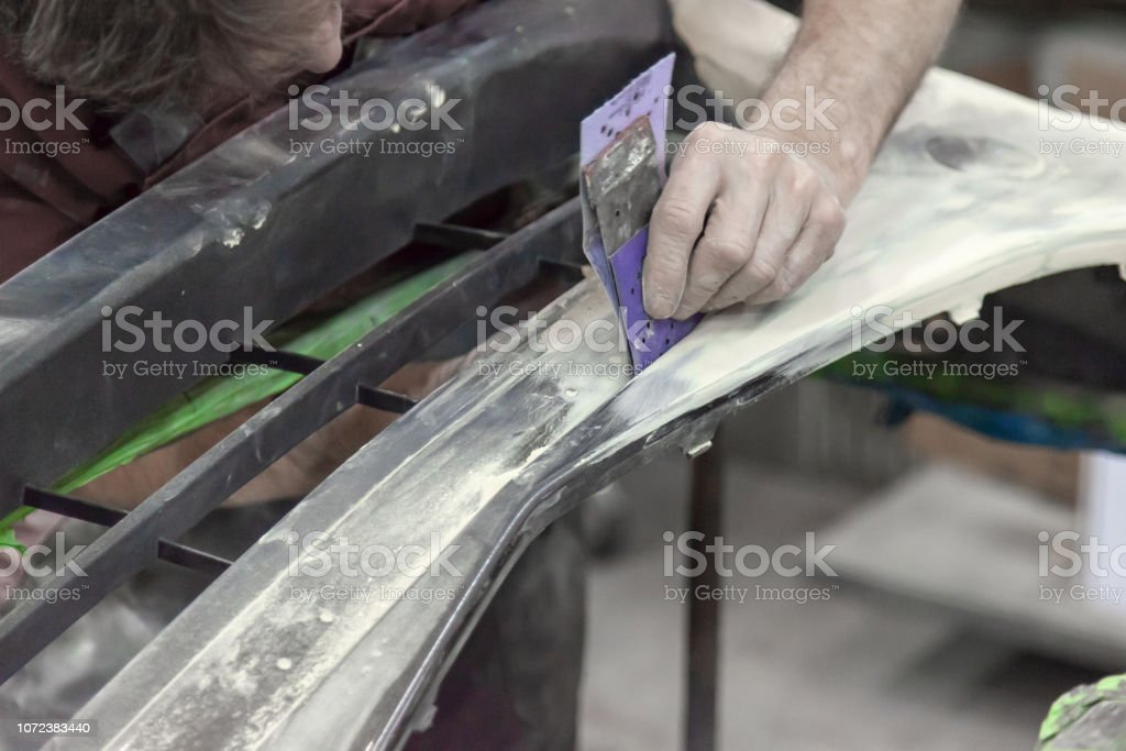 A man prepares a car body element for painting after an accident with the help of abrasive paper in a car repair shop. Recovery bumper after a collision. stock photo
