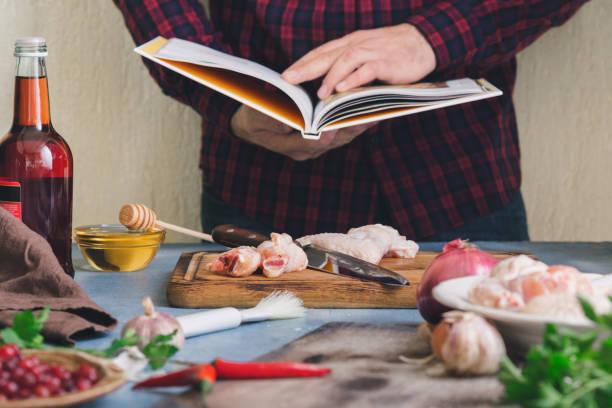 homem prepara asas de frango com molho de cranberry - receita - fotografias e filmes do acervo