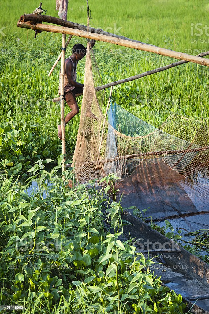 Man prepares Chinese fishing net, Majuli, Assam, India. royalty-free stock photo
