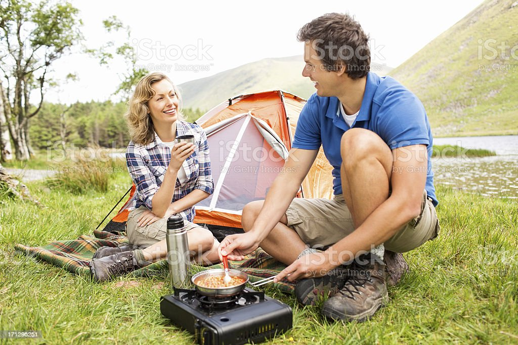 Man Prepares Food On Camping Stove stock photo